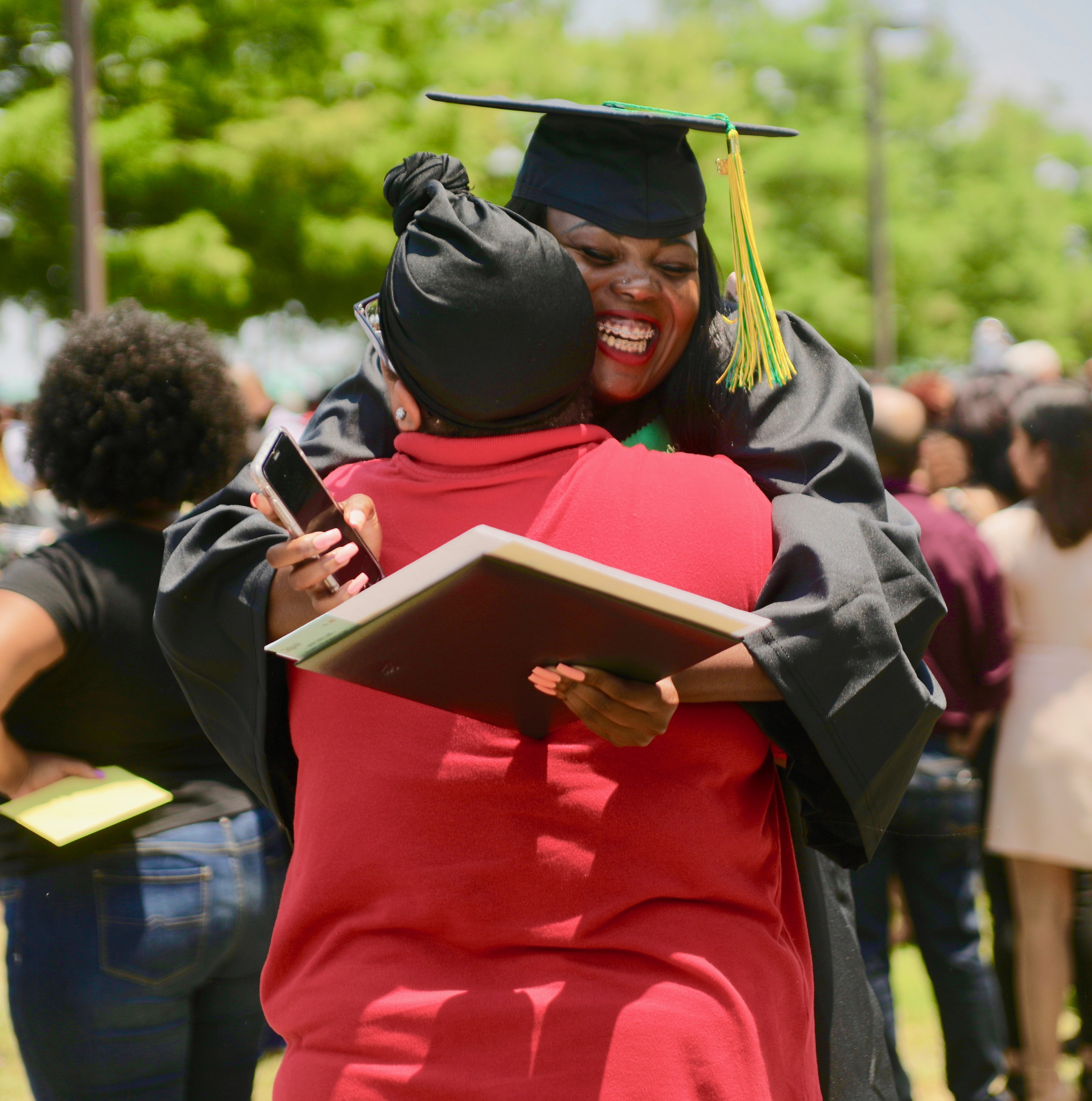 African-American female Delgado graduate smiling and hugging family member at commencement ceremony