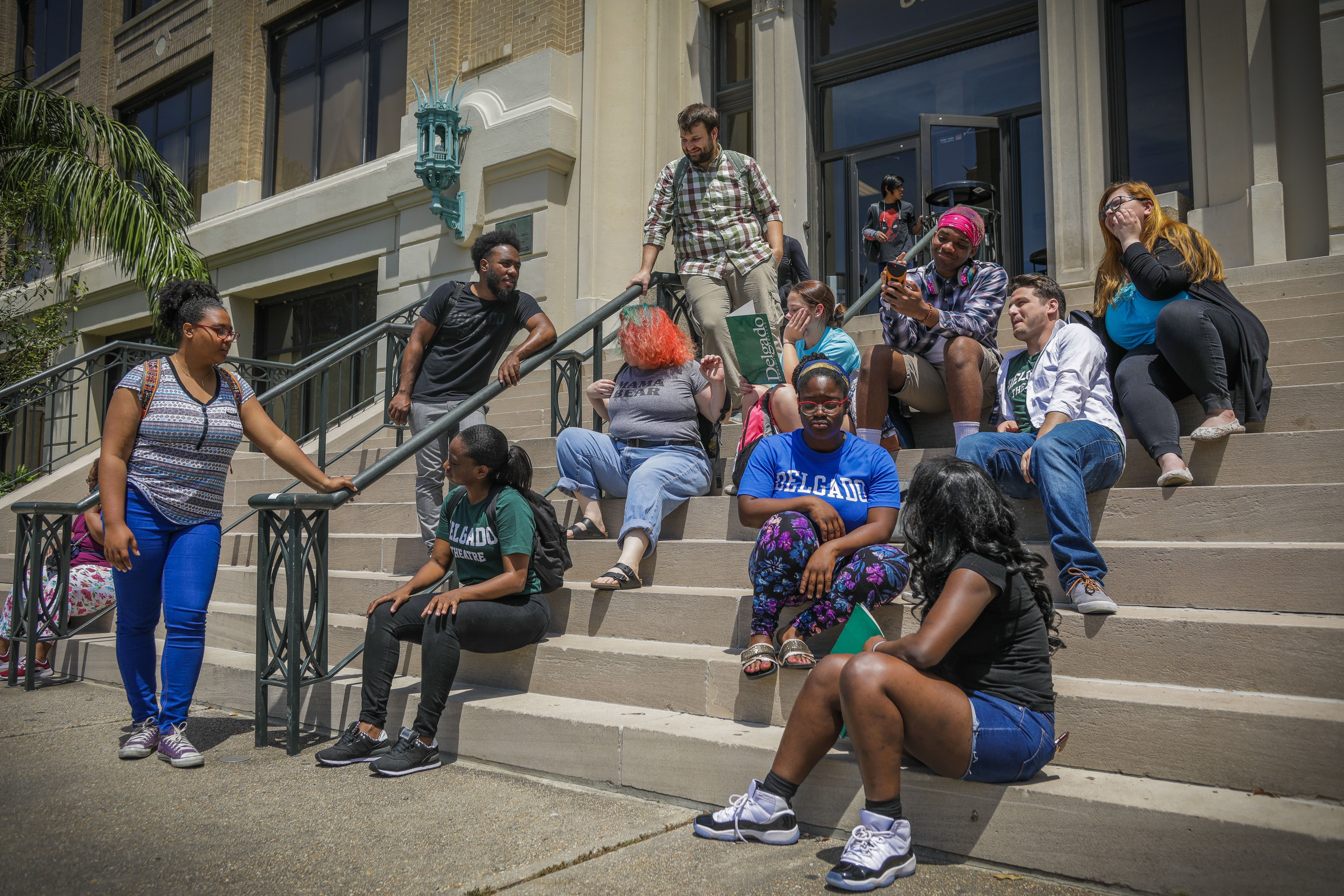 Diverse group of students socializing and studying on the steps of Isaac Delgado Hall (Building 1) at the City Park Campus